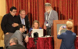 A group of six people stand around a computer and try to fix a problem at the MWXX conference in LA.