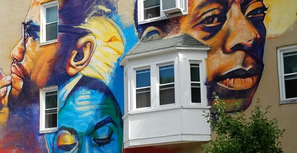 A mural on the side of a row house in the city of Baltimore.