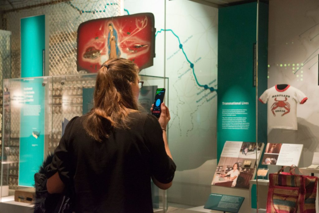 A woman with shoulder-length brown hair speaks or listens with her smartphone in a museum gallery setting.